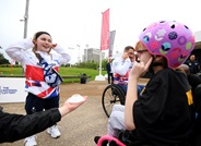 Ellie is standing opposite a young child in a wheelchair playing a game at the Olympic Park in London